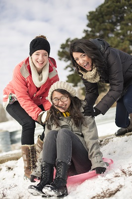 Students sledding at St. Mary's hill. Students outside in the snow in winter.