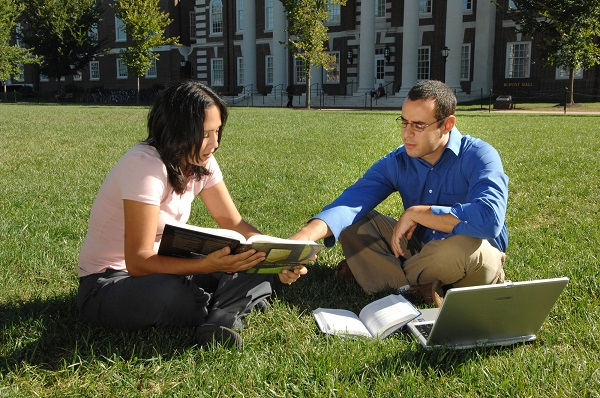 students sitting on the grass studying with laptop